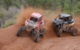 two Polaris RZRs racing on dirt track in WORCS